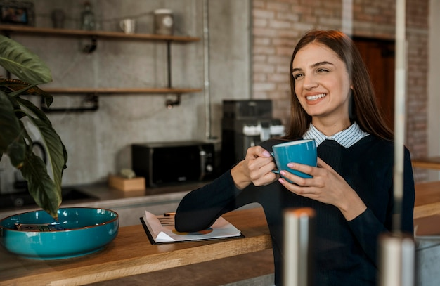 Smiley-frau, die während eines treffens kaffee trinkt
