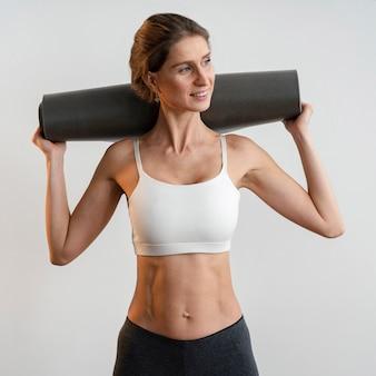 Smiley-frau, die yogamatte hält