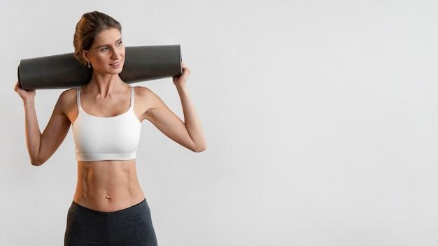 Smiley-frau, die yogamatte mit kopienraum hält