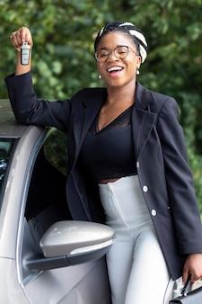 Smiley-frau hält ihre autoschlüssel hoch
