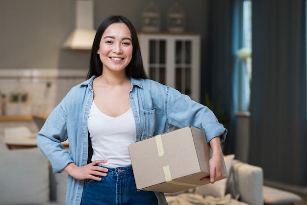 Smiley frau hält kisten, die sie online bestellt hat