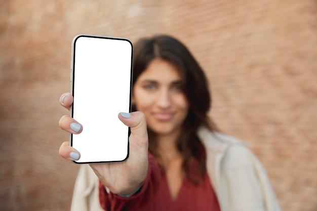 Smiley frau im freien hält smartphone