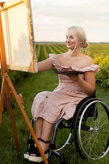Smiley-frau im rollstuhl, der draußen malt