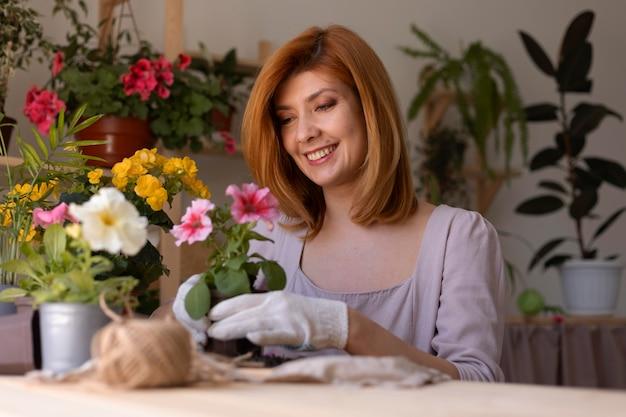 Smiley-frau kümmert sich um pflanze