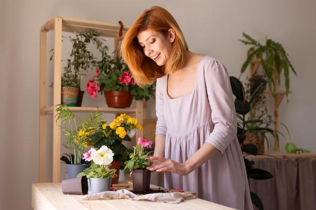 Smiley-frau kümmert sich um pflanzen mittlerer schuss
