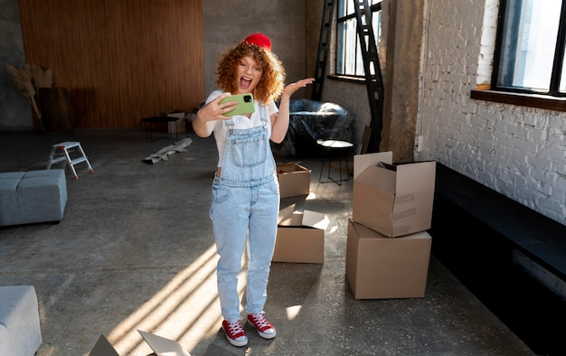 Smiley-frau macht selfie mit smartphone in ihrem neuen zuhause