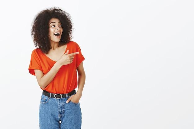 Smiley-frau mit afro-frisur, die im studio aufwirft