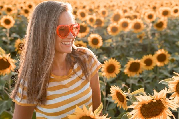 Smiley-frau mit herz formt sonnenbrille