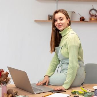 Smiley-frau mit laptop, der an einem blumenladen arbeitet