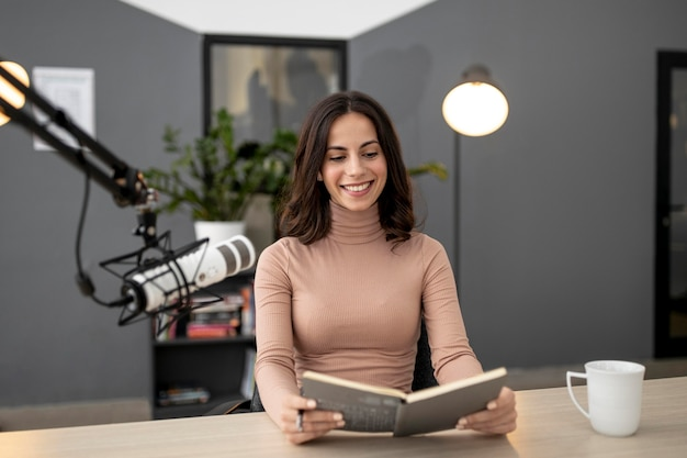 Smiley-frau mit mikrofon in einem radiostudio