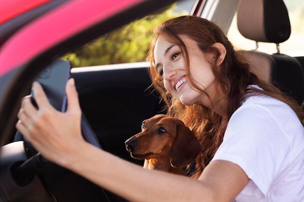 Smiley-frau mit mittlerem schuss, die selfie mit hund macht