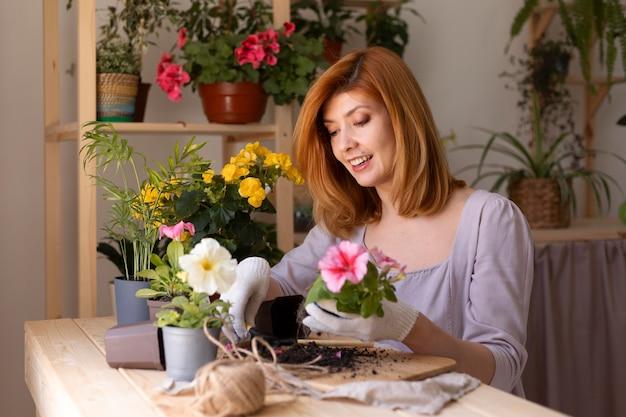 Smiley-frau mit mittlerem schuss, die sich um die pflanze kümmert