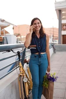 Smiley-frau mit mittlerer aufnahme, die am telefon telefoniert