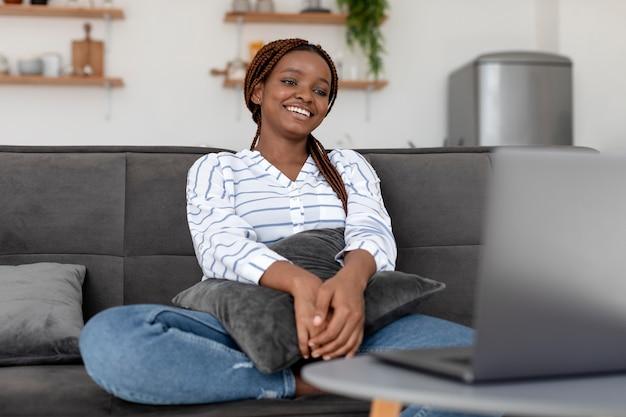 Smiley-frau mit mittlerer aufnahme, die auf der couch sitzt