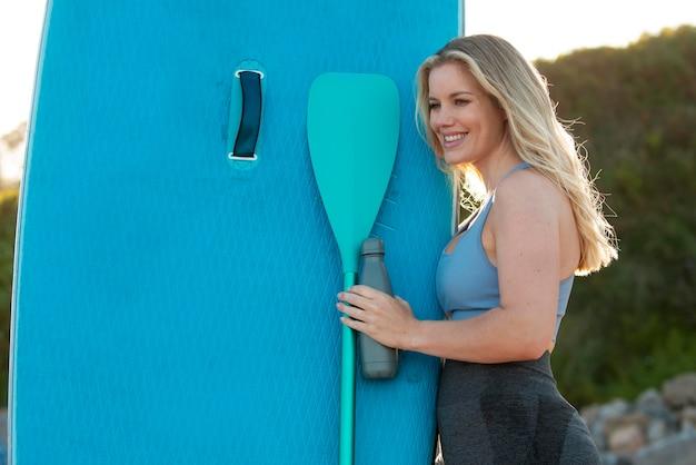 Smiley-frau mit paddleboard mittlerer schuss