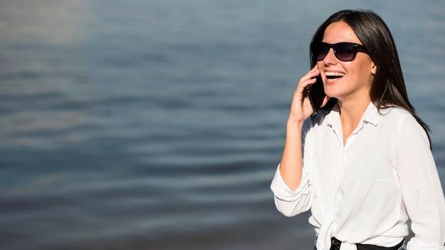Smiley-frau mit sonnenbrille, die am strand am telefon spricht