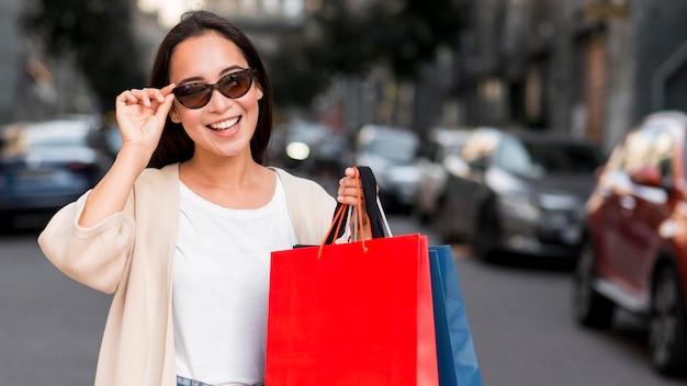 Smiley-frau mit sonnenbrille, die draußen mit einkaufstaschen aufwirft