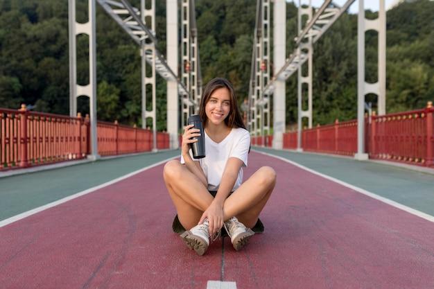 Smiley-frau mit thermoskanne, die auf brücke während des reisens aufwirft