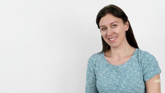 Smiley-frau mit verband am arm nach impfung