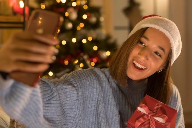 Smiley-frau mit weihnachtsmütze, die selfie nimmt, während sie weihnachtsgeschenk hält