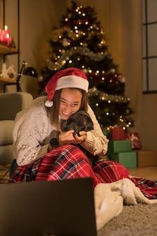 Smiley-frau mit weihnachtsmütze und ihrem hund, der laptop an weihnachten betrachtet