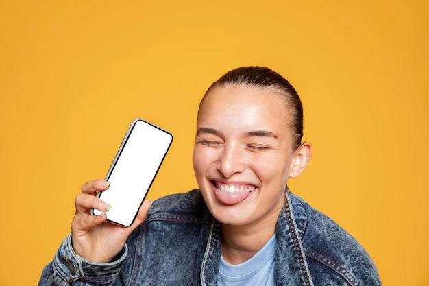 Smiley-frau mit zunge heraus, die smartphone hält