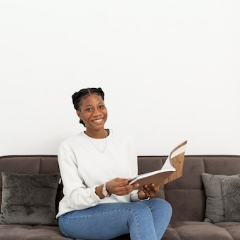 Smiley-frau sitzt auf der couch