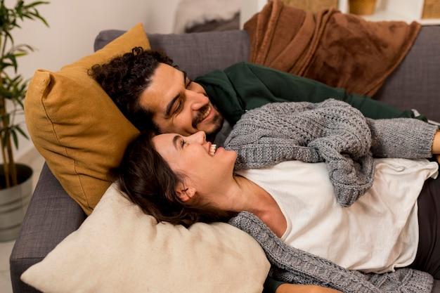 Smiley frau und ehemann liegen auf dem sofa