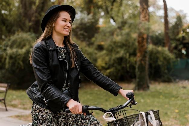 Smiley-frau und fahrrad im park