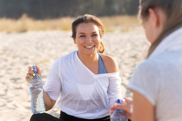 Smiley-frauen bleiben hydratisiert, während sie am strand trainieren