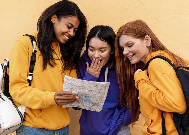 Smiley-frauen, die eine karte betrachten