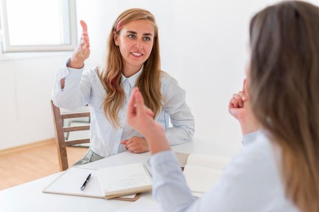 Smiley-frauen, die gebärdensprache verwenden, um zu kommunizieren