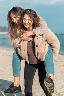 Smiley-frauen, die zusammen am strand aufwerfen