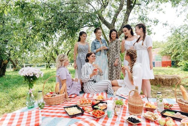 Smiley-frauen im freien, die sich auf einem picknick entspannen