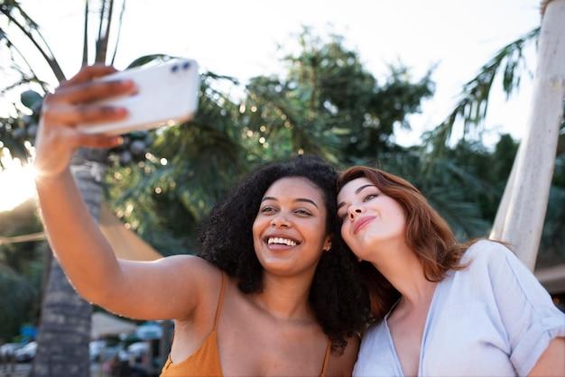 Smiley-frauen machen selfie mittlerer aufnahme