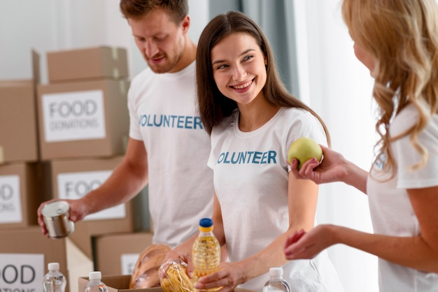 Smiley-freiwillige bereiten kisten mit lebensmittelspenden für wohltätige zwecke vor
