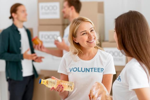 Smiley-freiwillige bereiten lebensmittel für die spende vor