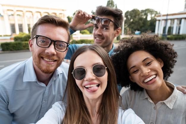 Smiley-freunde machen zusammen ein selfie im freien