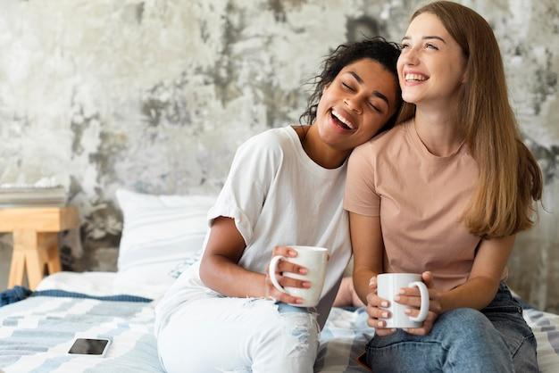 Smiley-freundinnen auf dem bett mit kaffee