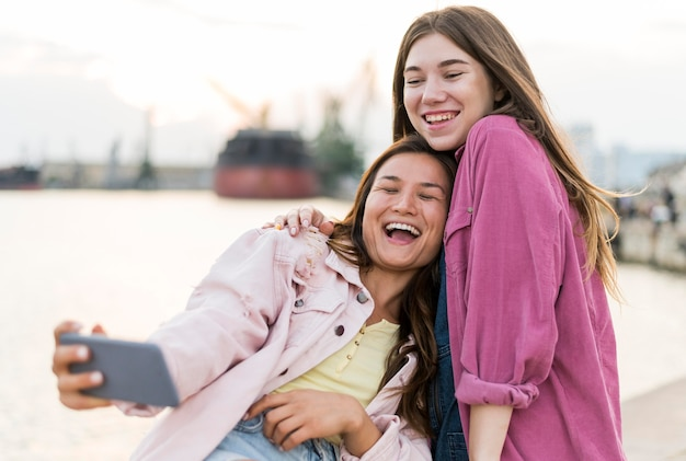 Smiley-freundinnen, die selfie am see nehmen