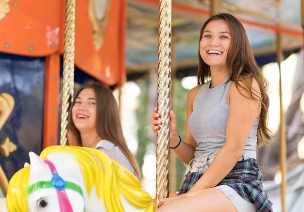 Smiley-freundinnen, die spaß auf dem karussell haben