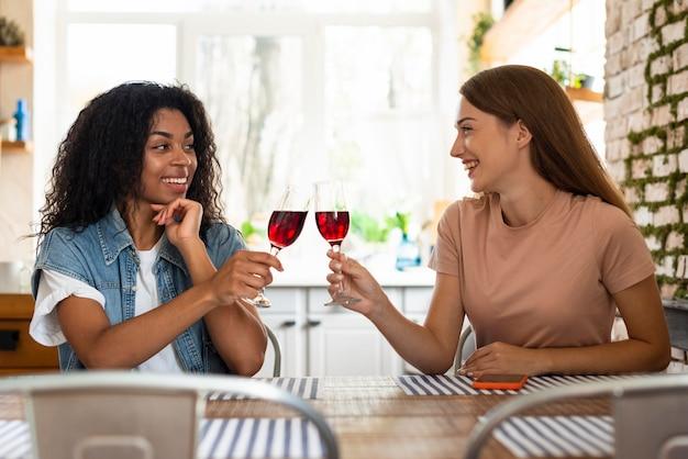 Smiley-freundinnen rösten zusammen ein glas wein