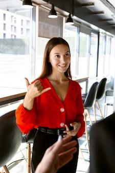 Smiley-geschäftsfrau, die gebärdensprache bei der arbeit verwendet