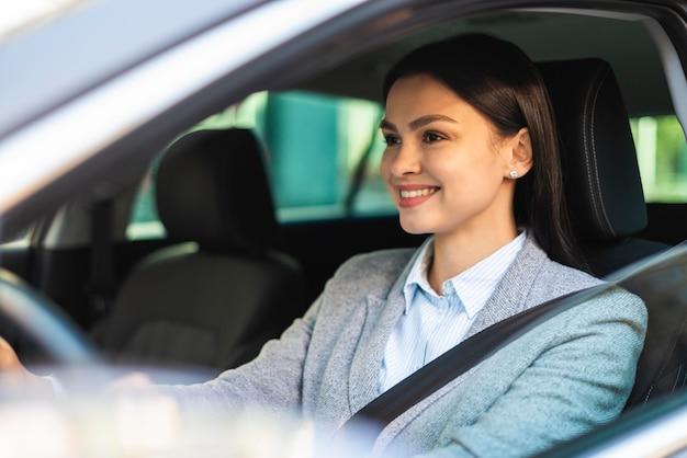 Smiley-geschäftsfrau, die ihr auto in der stadt fährt