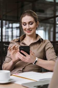 Smiley-geschäftsfrau, die ihr smartphone während einer besprechung verwendet