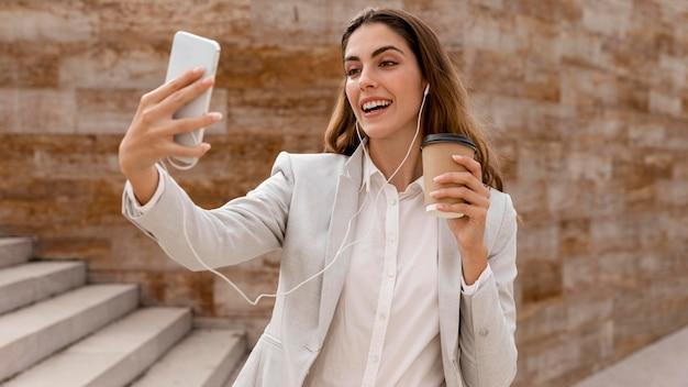 Smiley-geschäftsfrau, die selfie mit smartphone nimmt, während kaffeetasse hält