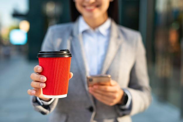 Smiley-geschäftsfrau, die smartphone beim kaffee verwendet