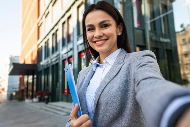 Smiley-geschäftsfrau mit zwischenablage, die ein selfie im freien nimmt