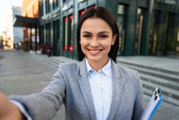Smiley-geschäftsfrau mit zwischenablage, die ein selfie in der stadt nimmt