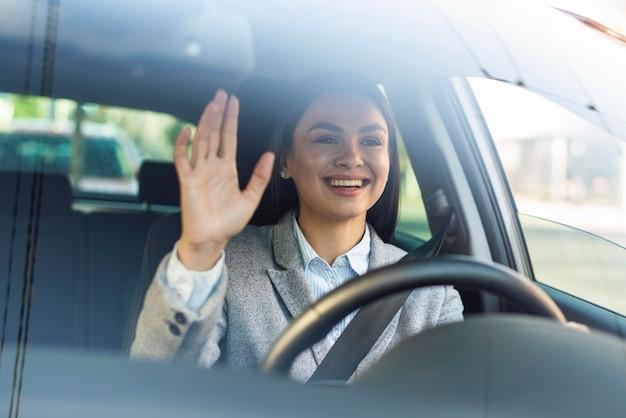 Smiley-geschäftsfrau winkt aus ihrem auto